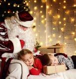 Santa Claus com as crianças bonitos pequenas felizes menino e menina perto da árvore de Natal Fotografia de Stock