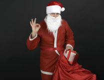 Santa Claus com o saco e as caixas de presente do Natal isolados no preto Imagens de Stock