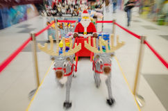 Santa Claus is coming. Santa Claus and two reindeers in front of a toys shop, dashing to meet the children and give them gifts. Figurines built from small parts Stock Photo