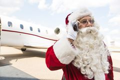 Santa Claus Communicating On Mobile Phone Against. Private jet at airport terminal Royalty Free Stock Photo