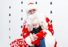 Santa Claus con el bebé en el cuarto blanco fotografía de archivo libre de regalías