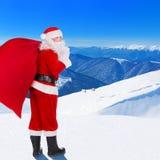 Santa Claus con el bolso de la Navidad contra tierra de la montaña del invierno de la nieve Fotografía de archivo libre de regalías