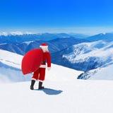 Santa Claus con el bolso de la Navidad contra tierra de la montaña del invierno de la nieve Fotografía de archivo