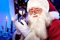 Santa Claus con el reloj de arena Imágenes de archivo libres de regalías