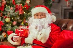 Santa Claus con giftbox su fondo dell'abete scintillare Chr immagini stock libere da diritti