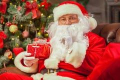 Santa Claus con giftbox su fondo dell'abete scintillare Chr fotografia stock libera da diritti