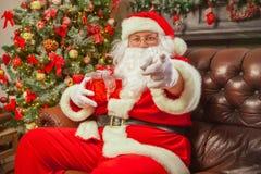 Santa Claus con giftbox su fondo dell'abete scintillare Chr immagini stock