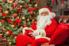 Santa Claus con giftbox su fondo dell'abete scintillare Chr fotografie stock libere da diritti