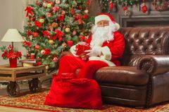 Santa Claus con giftbox su fondo dell'abete scintillare Chr immagine stock