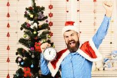 Santa Claus con il fronte felice dei vincitori vicino all'albero di Natale immagini stock