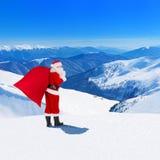 Santa Claus con il sacco di Natale contro le montagne di inverno e uff Immagine Stock