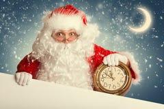 Santa Claus con la bandera en blanco blanca que sostiene un reloj Foto de archivo
