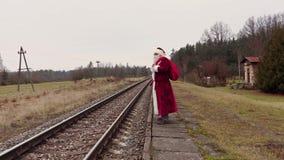 Santa Claus con la borsa del regalo sulla piattaforma vicino alla ferrovia video d archivio