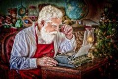 Santa Claus con la macchina da scrivere in officina Immagini Stock Libere da Diritti