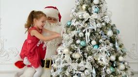 Santa Claus con la niña bonita que adorna el árbol de navidad almacen de metraje de vídeo