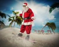 Santa Claus con la snowboard en una playa foto de archivo