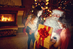 Santa Claus con los presentes de la magia y niños fotografía de archivo