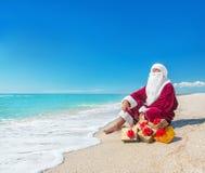 Santa Claus con molti regali dorati che si rilassano alla spiaggia - christma Fotografia Stock Libera da Diritti