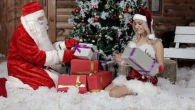 Santa Claus con su nieta arregla los regalos debajo del árbol de navidad metrajes