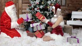 Santa Claus con su nieta arregla los regalos debajo del árbol de navidad almacen de metraje de vídeo
