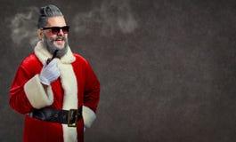 Santa Claus con un'acconciatura e un sigaro lancia un fumo fotografie stock libere da diritti