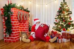 Santa Claus con un bolso de los regalos que se sientan en el piso en un cuarto w Imagen de archivo libre de regalías