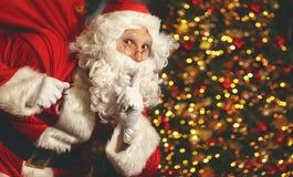 Santa Claus con un bolso de regalos en el árbol de navidad Fotografía de archivo libre de regalías