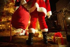 Santa Claus con un bolso por la chimenea el día de la Navidad back Fotos de archivo libres de regalías