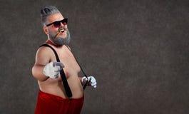 Santa Claus con un cigarro desnudo del vientre en sus dientes contra fotografía de archivo