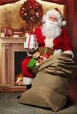 Santa Claus con una borsa dei presente al camino Fotografia Stock Libera da Diritti