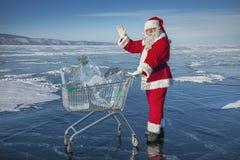 Santa Claus con una carretilla del hielo puro en el lago Baikal del invierno Foto de archivo libre de regalías