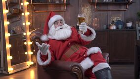 Santa Claus congratulates on Christmas and drinks a glass of beer