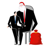 Santa Claus congratulates employee. Manager sitting on lap of bo Royalty Free Stock Images