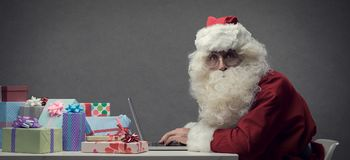 Santa Claus connecting with his laptop. Santa Claus connecting and working online with his laptop, he is preparing gifts and shopping online on Christmas Eve Stock Image