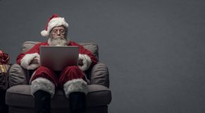 Santa Claus connecting with a laptop. Santa claus relaxing at home and connecting with a laptop, he is chatting and social networking, Christmas time and stock images