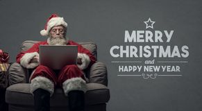 Santa Claus connecting with a laptop. Santa claus relaxing at home and connecting with a laptop, he is chatting and social networking,Christmas card with wishes Royalty Free Stock Photo