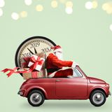 Santa Claus countdown on car. Christmas countdown arriving. Santa Claus on car delivering New Year gifts and clock at green background stock image