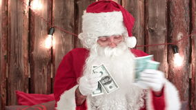 Santa Claus counting his money and showing money disappearing trick stock video
