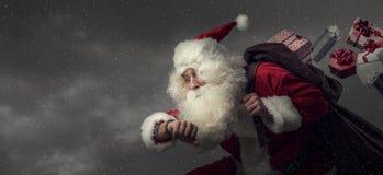 Santa Claus courant et livrant des cadeaux images libres de droits