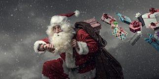 Santa Claus courant et livrant des cadeaux Image stock