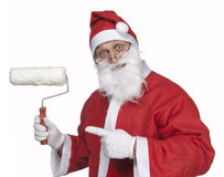 Santa claus craftman. Santa claus holding and pointing at a paint roller Royalty Free Stock Photos