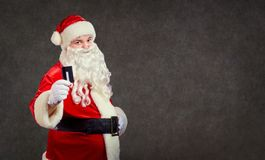Santa Claus with a credit card on a background for text. royalty free stock images
