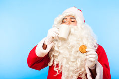 Santa claus with a cup of coffee or tea and a biscuit on blue ba Stock Image