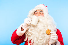 Santa claus with a cup of coffee or tea and a biscuit on blue ba Royalty Free Stock Image