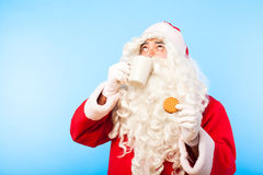 Santa claus with a cup of coffee or tea and a biscuit on blue ba Royalty Free Stock Images