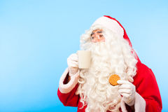 Santa claus with a cup of coffee or tea and a biscuit on blue ba Royalty Free Stock Photography