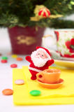 Santa claus with cup of tea. Lucky small santa claus with cup of tea and sweetmeat on background fir tree Royalty Free Stock Image
