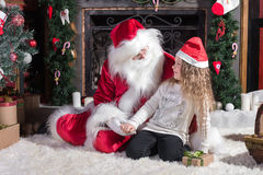 Santa Claus and cute girl getting ready for Christmas. Stock Image