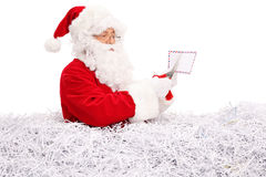 Santa Claus cutting a letter with scissors Stock Photography