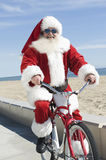 Santa Claus Cycling By Beach. Portrait of a happy Santa Claus cycling by beach against cloudy sky royalty free stock photos